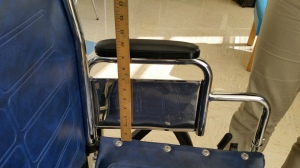 Measurements are being taken from the overall height of the wheelchair.