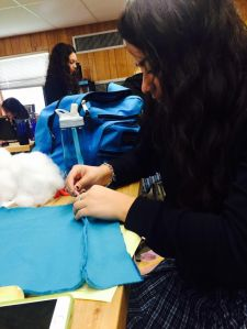 This photo was taken by Dayanne A.. Lourdes is diligently sewing part of the blanket.