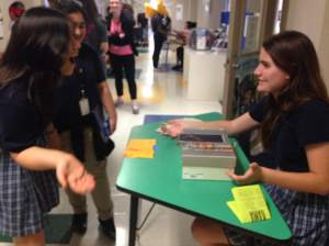 Original photo by Erin Simons of Eliza talking to a student about her product