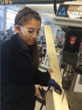 Sara Espinosa drilling holes into one of our planks.